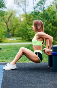 Woman Doing Triceps Dip Exercise On City Street Bench.