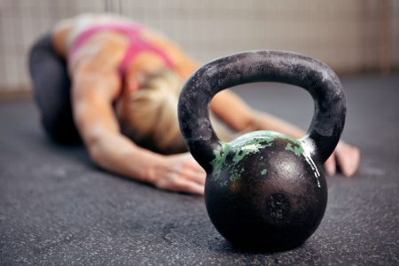 female stretching with kettlebelll