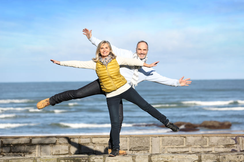 two people balancing on beach