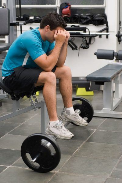 Man with head down in weight room