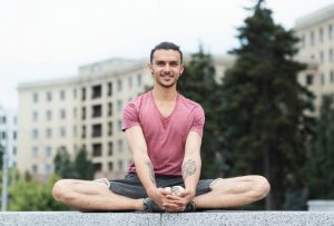 Portrait Of Young Men Doing Butterfly Yoga Pose Outdoors