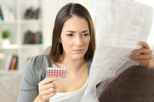 Worried Woman Reading Contraceptive Pills Leaflet