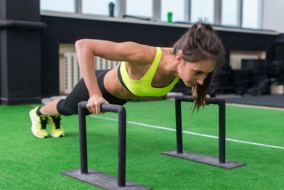 Young Fit Woman Doing Horizontal Push Ups With Bars In Gym.