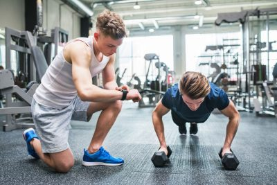 Young Fit Men In Gym Doing Push Ups On Dumbbells, Measuring Time On Smartwatch.