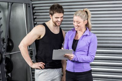 Female Trainer Talking With Client At Crossfit Gym